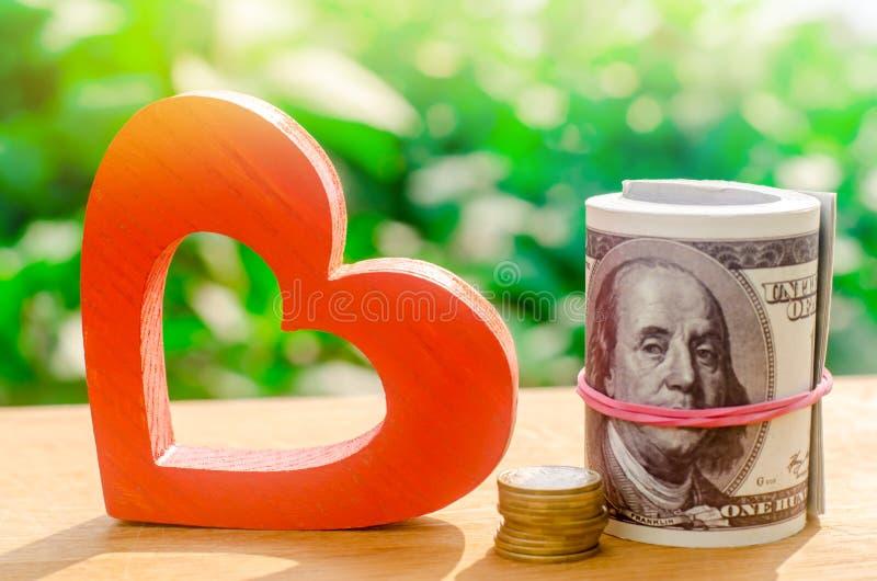 Czerwony drewniany serce i pieniądze Pojęcie oszczędzania i akumulacji pieniądze Zdrowie dobroczynność darowizna Zakupy walentynk obraz stock