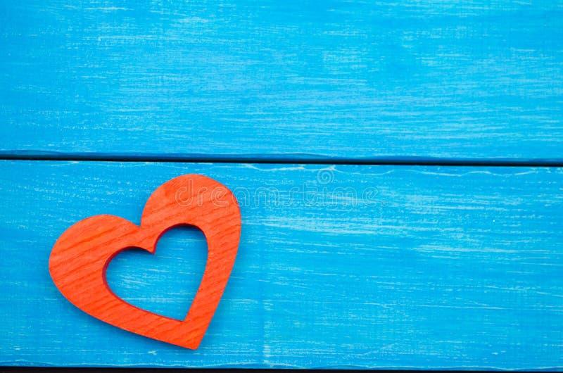 Czerwony drewniany serce na błękitnym tle, walentynki ` s dzień Pojęcie miłość zdjęcia stock