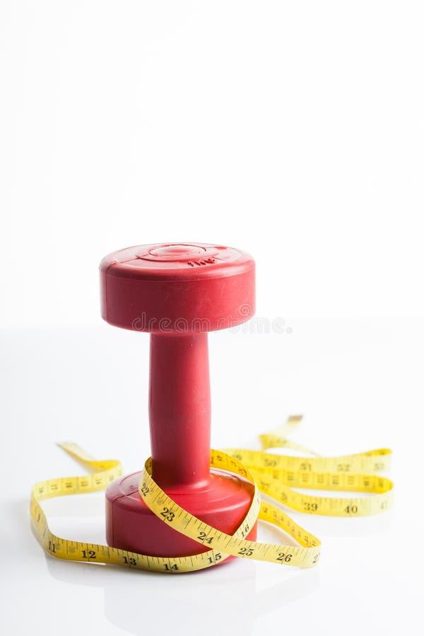 Czerwony dumbbells ciężar z pomiarową taśmą zdjęcia stock