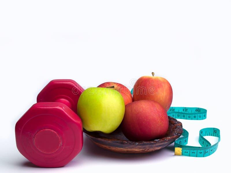 Czerwony dumbbells ciężar z pomiarową taśmą i jabłkiem zdjęcie stock