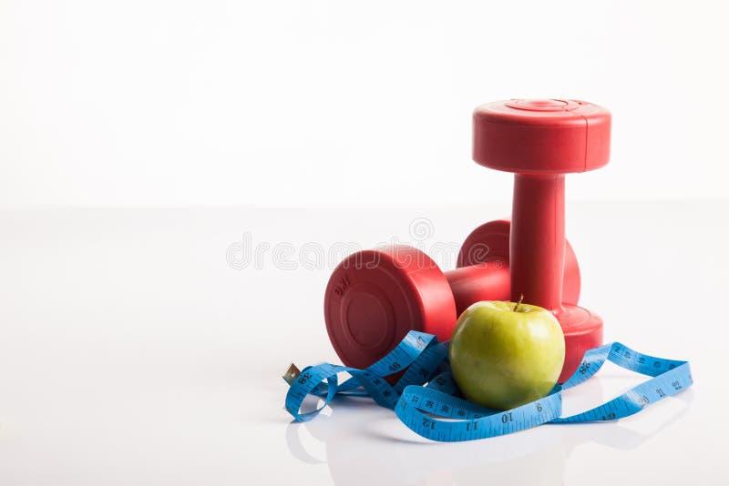 Czerwony dumbbells ciężar z pomiarowym taśmy i zieleni jabłkiem obraz stock