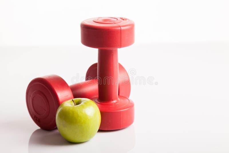 Czerwony dumbbells ciężar z zielonym jabłkiem obrazy stock
