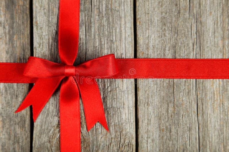 Czerwony faborek z łękiem na popielatym drewnianym tle zdjęcie stock