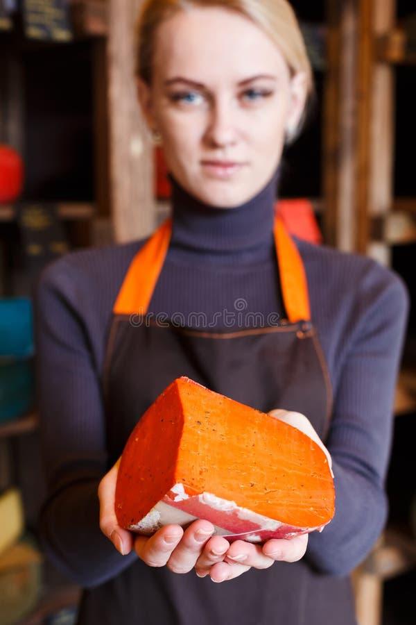Czerwony gouda ser w sklepowego asystenta rękach zdjęcie royalty free