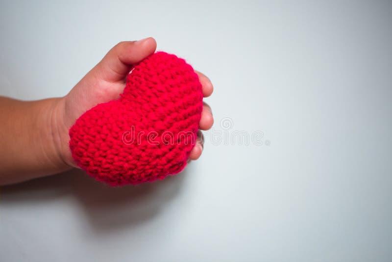 Czerwony hearth w dziecko ręce na białym tle obrazy stock