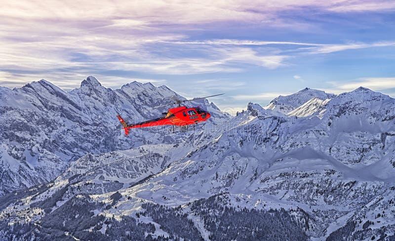 Czerwony helikopter przy szwajcarskimi alps blisko Jungfrau góry zdjęcia stock