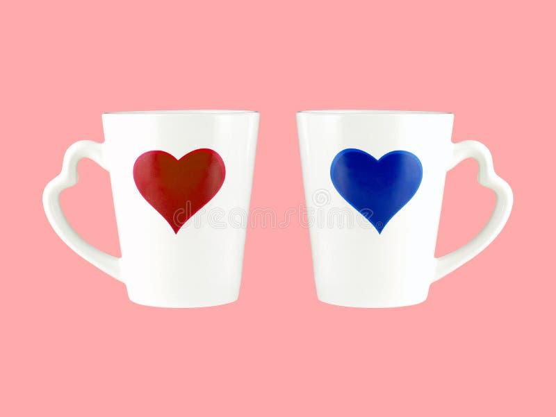 Czerwony i błękitny kierowy kształt na białej filiżance z serce kształtującą rękojeścią odizolowywającą na różowym tle zdjęcia royalty free