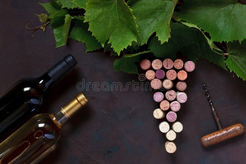 Czerwony i biały wino w butelek, korków, corkscrew i winogrona liściach, zdjęcia stock