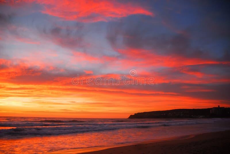 Czerwony i pomarańczowy słońce wzrost nad plażą zdjęcia royalty free
