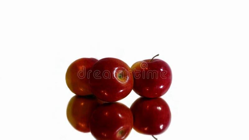 Czerwony jabłka kłamstwo na odbija powierzchni obraz stock