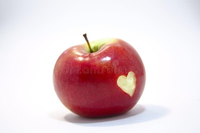 Czerwony jabłko na białym tle z cięciem za sercu na swój stronie, obraz stock