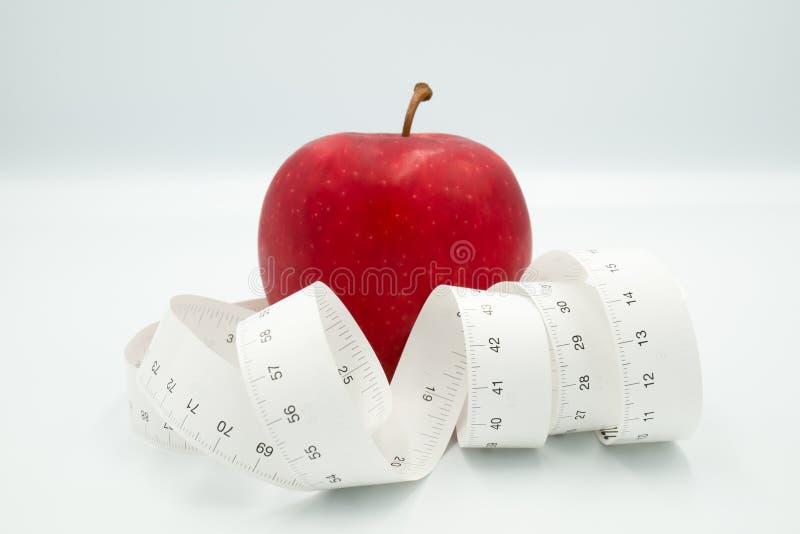 Czerwony jab?ko i miara nagrywamy centymetr kt?ry reprezentuje zmniejsza, ?wiczy dla cia?a w dobrym stanie projekta poj?cia i ci? obraz stock