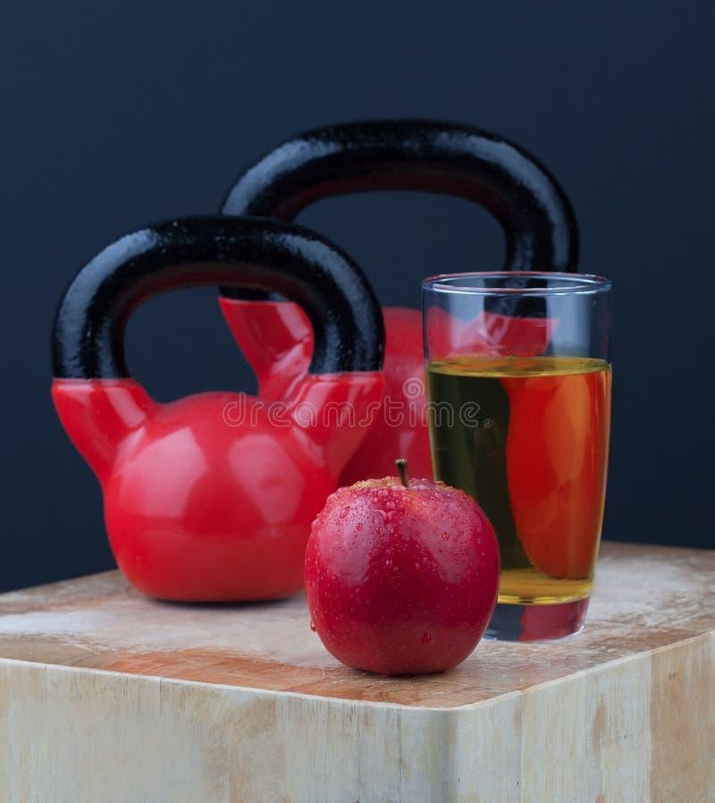 Czerwony jabłko, sok i kettlebells na ciapanie desce, obraz stock