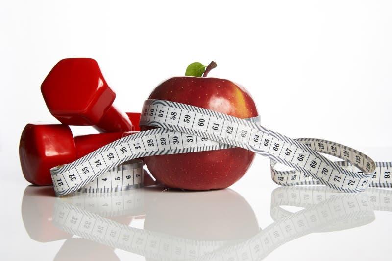 Czerwony jabłko z pomiarowymi taśmy i ciężaru dumbbells zdjęcie royalty free
