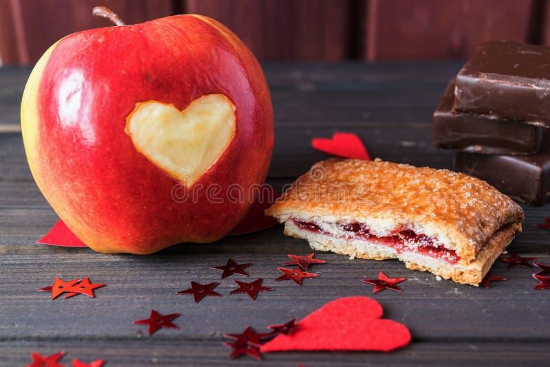 Czerwony jabłko z sercem rzeźbiącym dalej, czereśniowym kulebiakiem i czekoladowymi barami dekorującymi z małym czerwonym gwiazdy zdjęcia royalty free