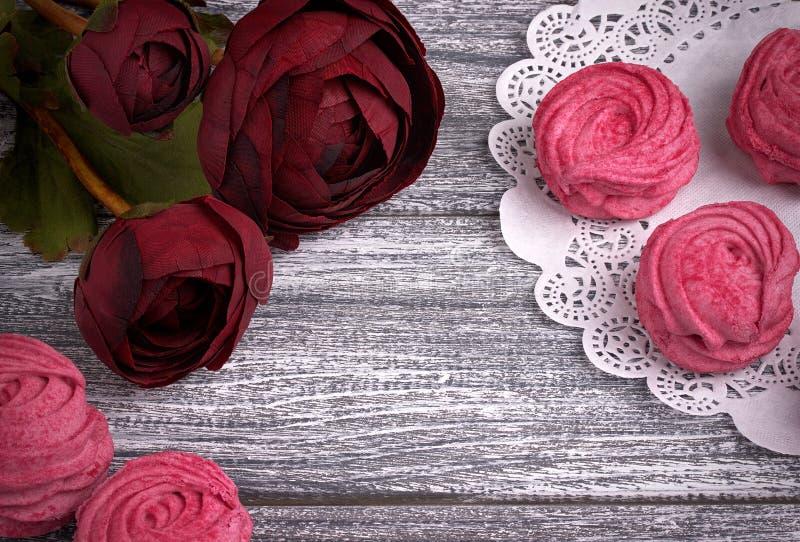 Czerwony jaskier kwitnie ranunculus białych i różowych zephyr marshmallows koronkową papierową pieluchę na szarym drewnianym tle  fotografia stock