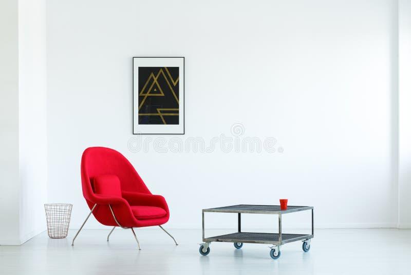 Czerwony karło obok przemysłowego stołu w prostym białym mieszkaniu zdjęcia stock
