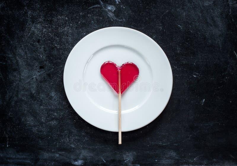 Czerwony kierowy kształtny lizak na talerzu - valentines dzień obrazy royalty free