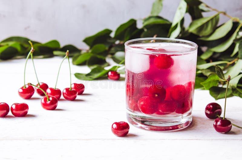 Czerwony koktajl z wiśnią i lodem na białym drewnianym tle Świeży lato koktajl z wiśniami i kostka lodu zdjęcie stock