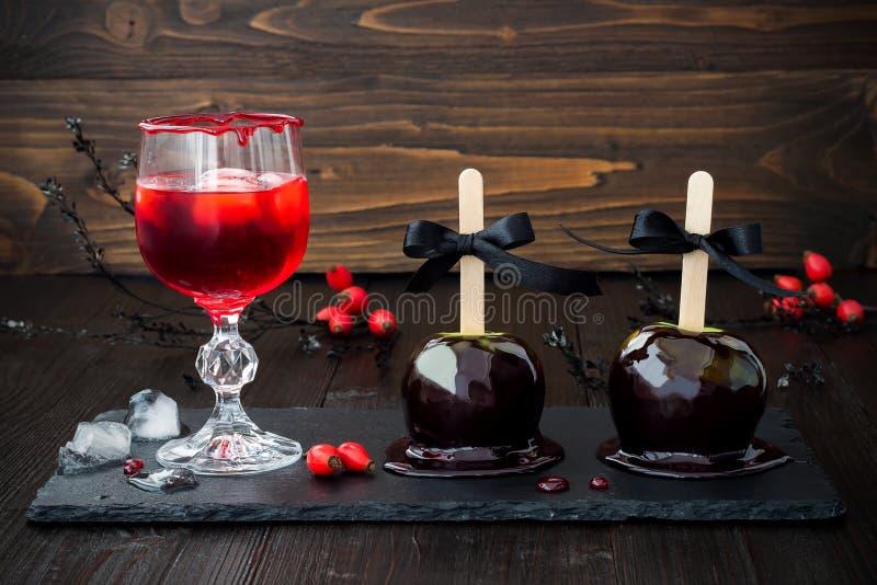Czerwony krwisty wampira koktajl i czarni jadu karmelu jabłka Tradycyjny deserowy przepis dla Halloween przyjęcia zdjęcia stock