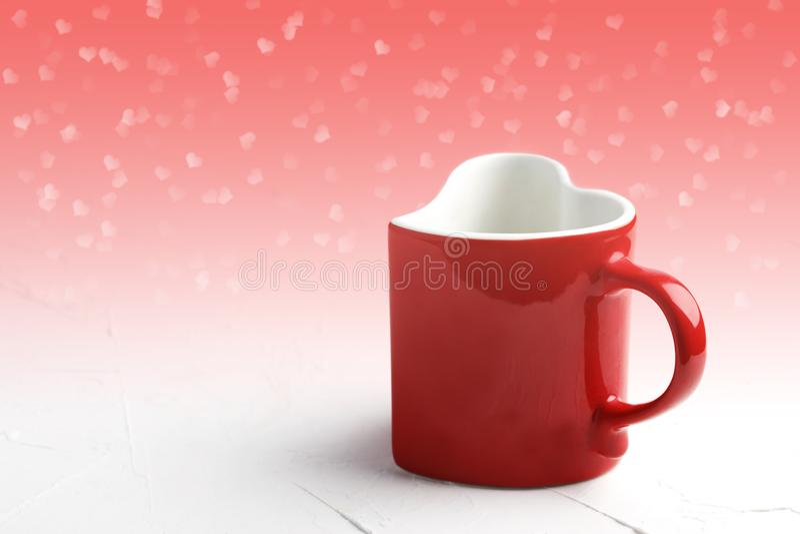Czerwony kubek w kształcie serce na bielu stole przy lekkim czerwonym tłem obraz stock
