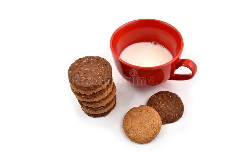 Czerwony kubek z mlekiem i ciastka zaopatrujemy wizerunki fotografia stock