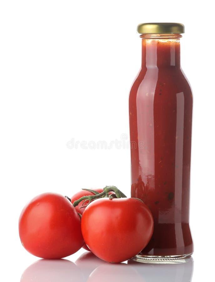 Czerwony kumberland w świeżych pomidorach na białym odosobnionym tle i butelce Domowej roboty pomidorowy kumberland ketchup zdjęcie stock