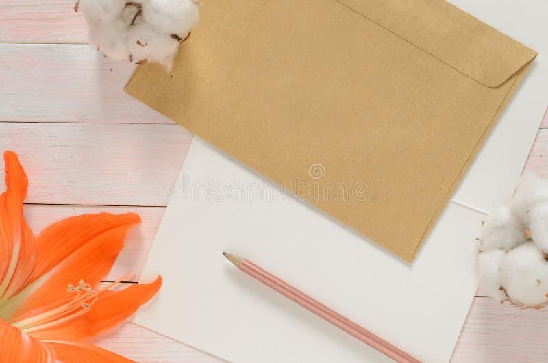 Czerwony kwiat w rogu z papierową kopertą i bawełną, pióro na jasnoróżowym tle zdjęcie stock