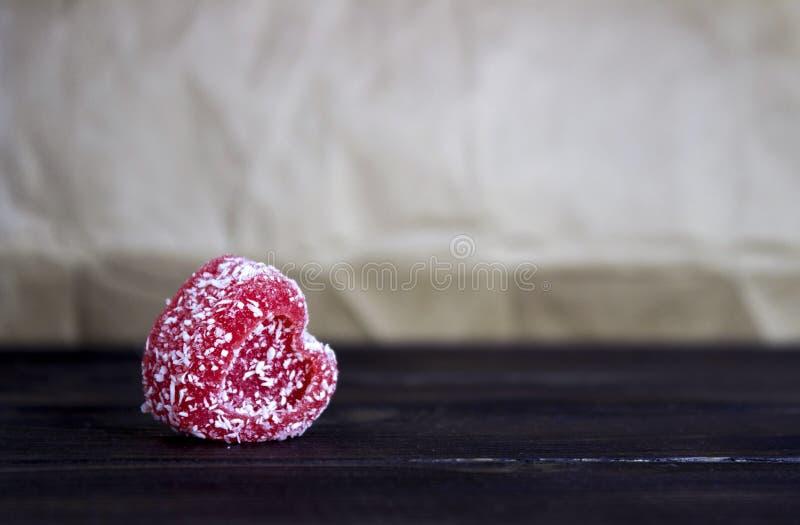 Czerwony marmoladowy w kokosowym goleniu w postaci serca na drewnianym tle fotografia stock