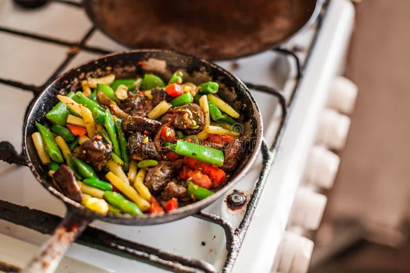Czerwony mięso z warzywami w starej dłoniak niecce na kuchence obrazy stock