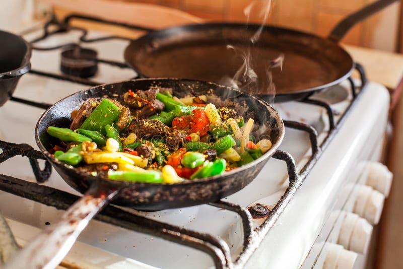 Czerwony mięso z warzywami w starej dłoniak niecce na kuchence fotografia royalty free