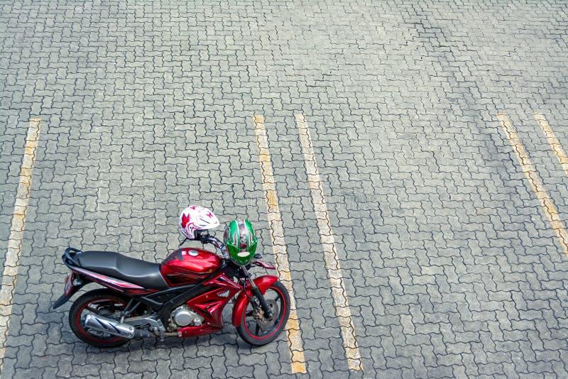 Czerwony motocykl na pustym samochodowym parking bruku zdjęcia royalty free