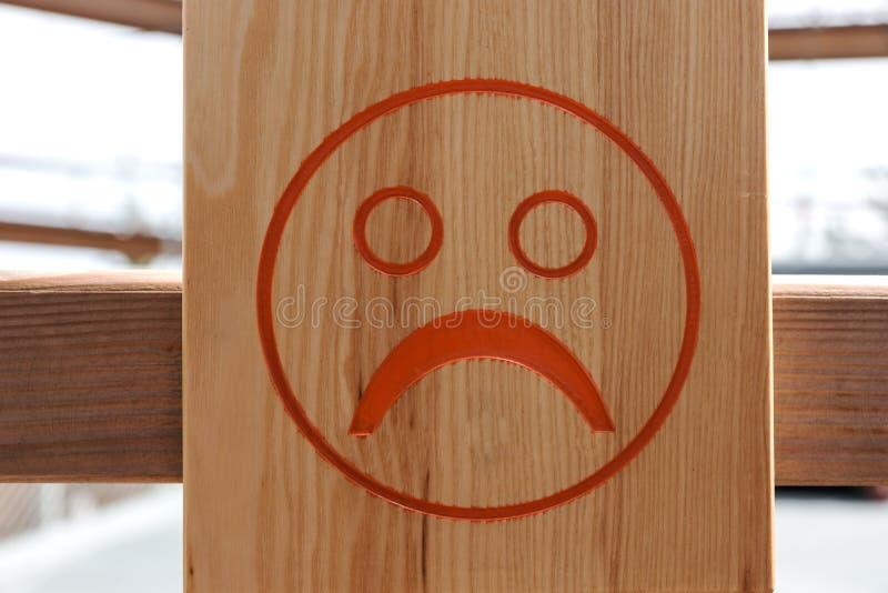 Czerwony nieszczęśliwy smiley na drewnianym tle obraz royalty free