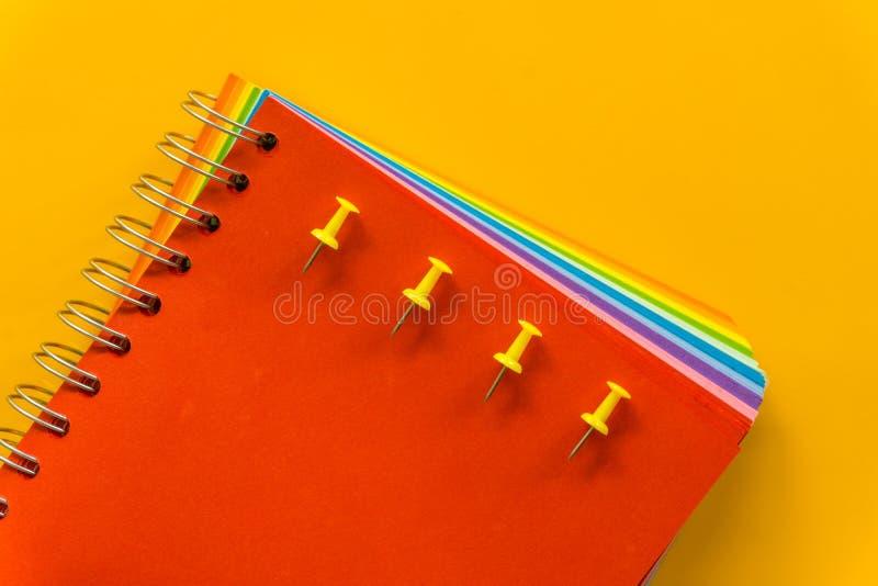 Czerwony notatnik na Żółtym Pastelowych menchii tle obrazy royalty free
