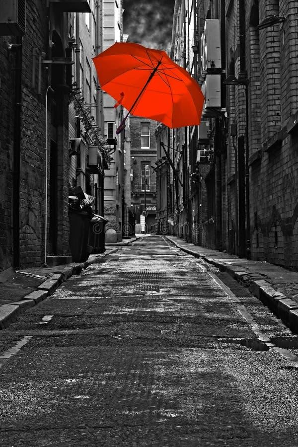 Czerwony parasol w zmroku z powrotem ulicie fotografia stock