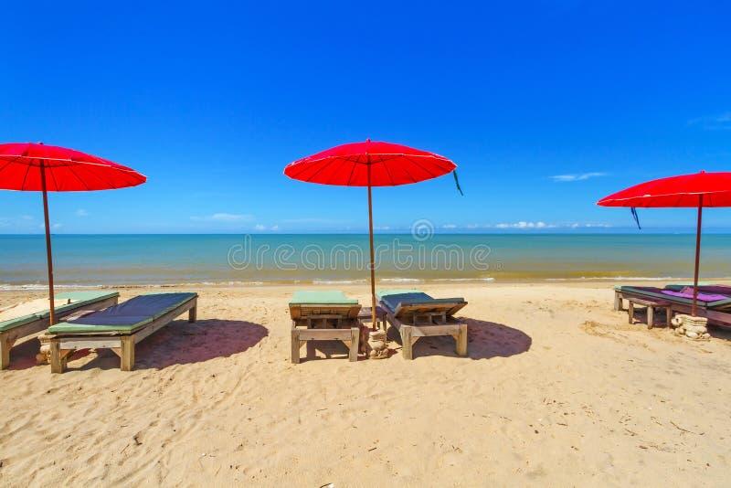 Czerwony parasol z deckchair na tropikalnej plaży obrazy stock