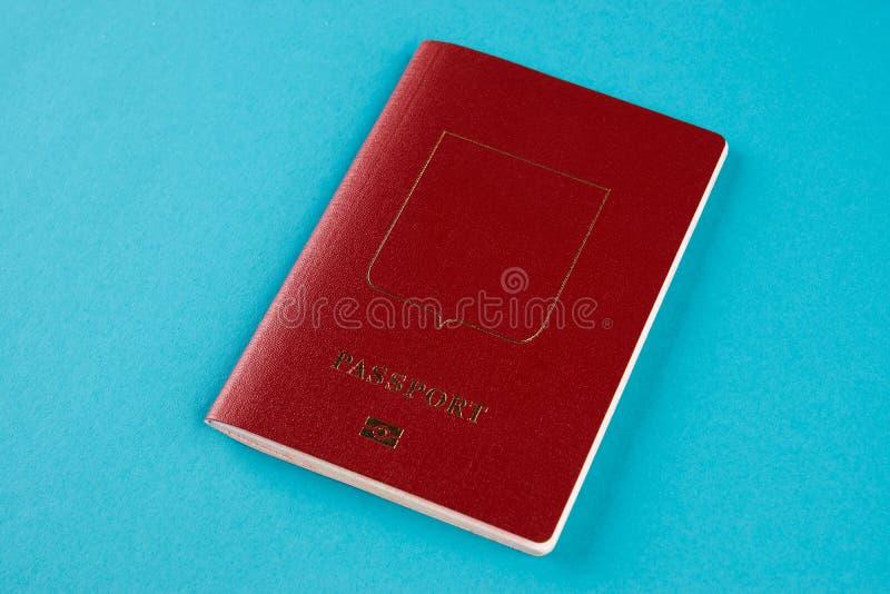 Czerwony paszportowy dokument podróżny na błękitnym tle obraz stock