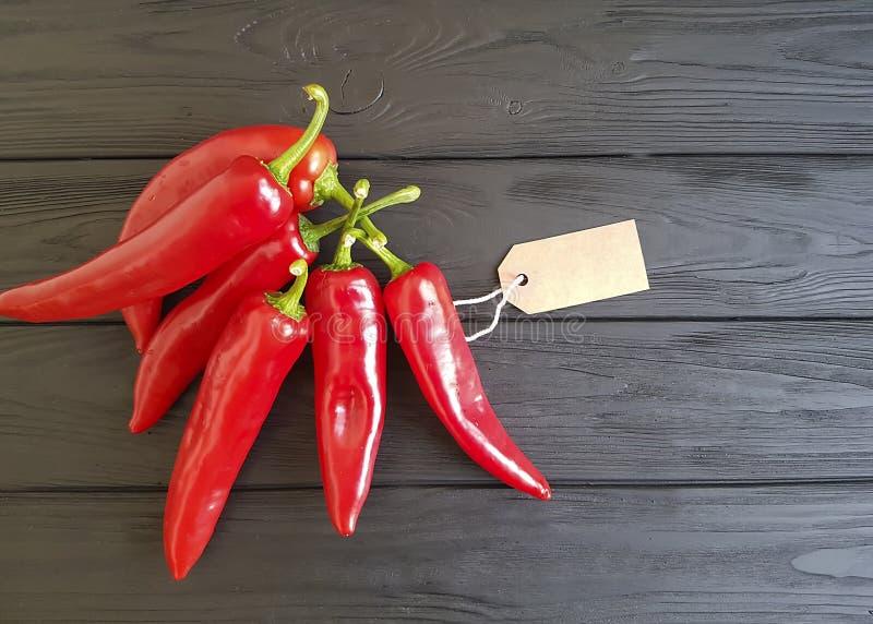 Czerwony pieprz na czarnej drewnianej etykietce kulinarnej obrazy royalty free