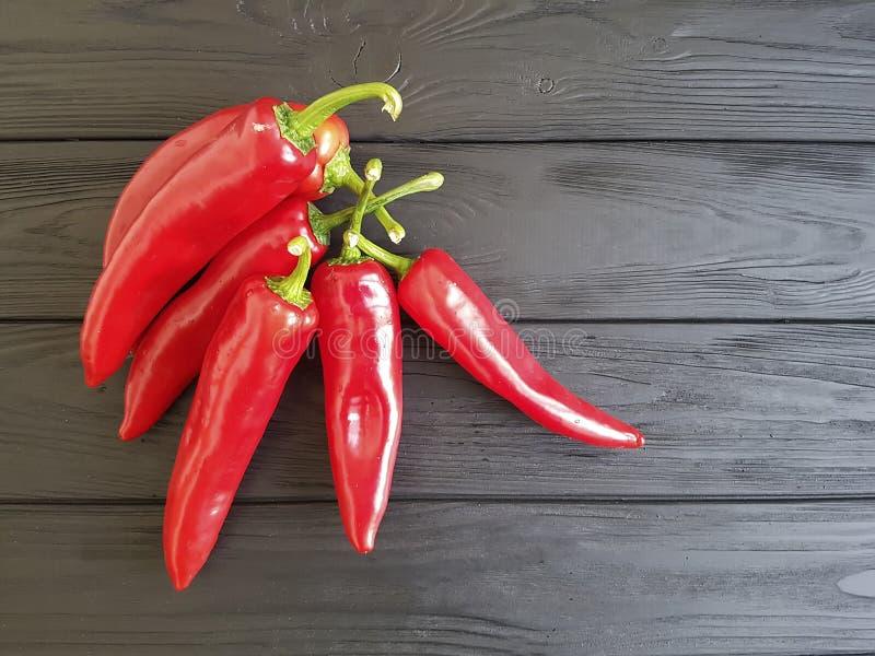 Czerwony pieprz na czarnym drewnianym kulinarnym cookery obrazy royalty free