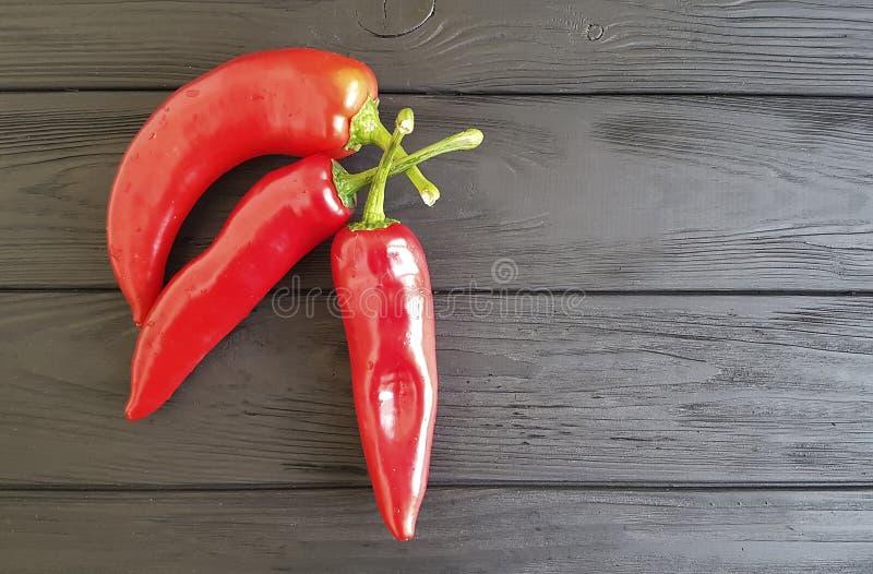 Czerwony pieprz na czarnym drewnianym kulinarnym cookery roczniku obrazy royalty free