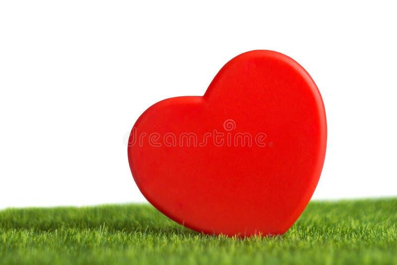 Czerwony plastikowy serce na zielonej imitacji trawa fotografia stock