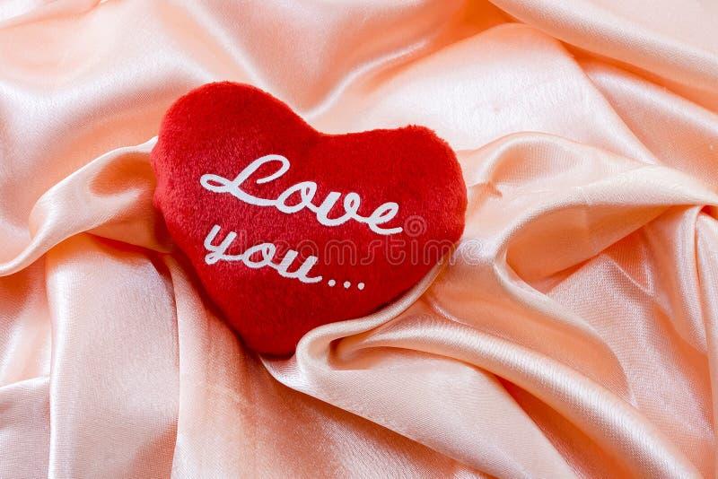 Czerwony pluszowy serce z inskrypcją: kocha ciebie zdjęcia royalty free