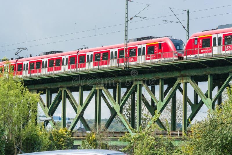 Czerwony pociąg ekspresowy na kolejowym moscie w Essen Kettwig fotografia stock