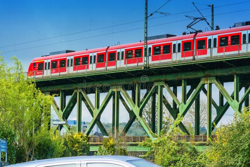 Czerwony pociąg ekspresowy na kolejowym moscie w Essen Kettwig obraz stock