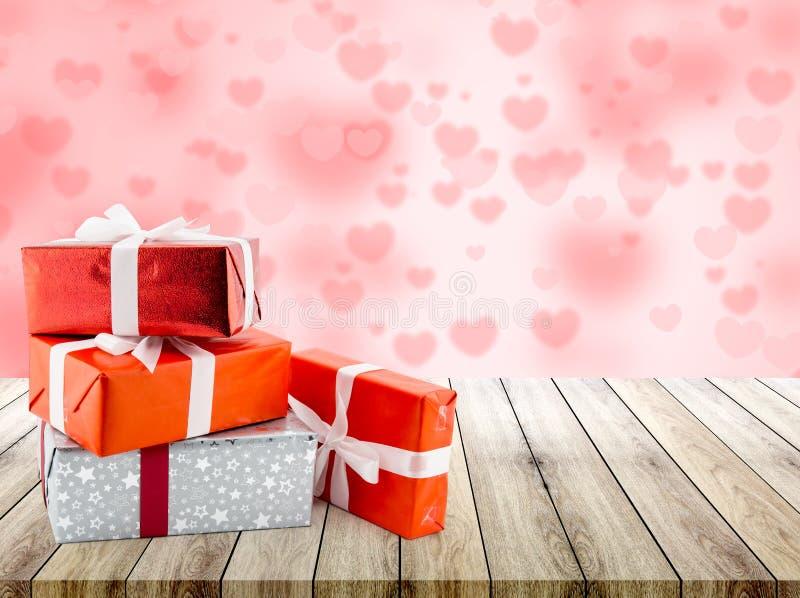 Czerwony prezenta pudełko i kierowy kształt na drewnianym stołowym wierzchołku z kierowym plamy bokeh tłem zdjęcie royalty free