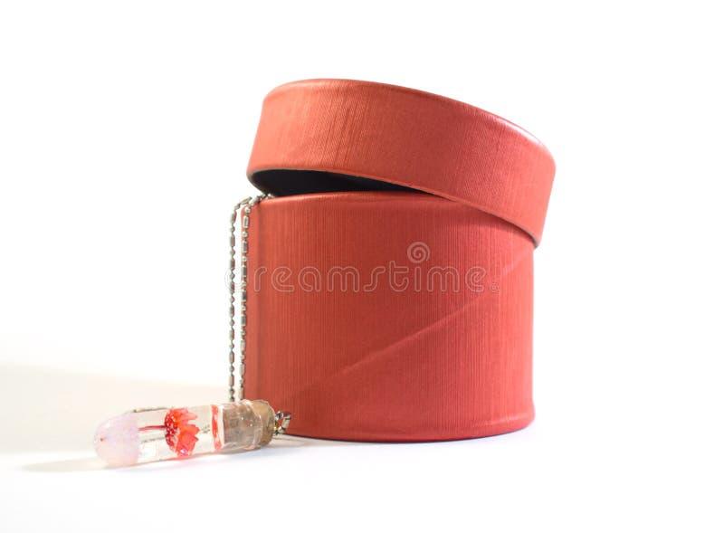 Czerwony prezenta pudełko, kolia z stoppered żarówką i czerwonym kwiatem w eterze i fotografia stock