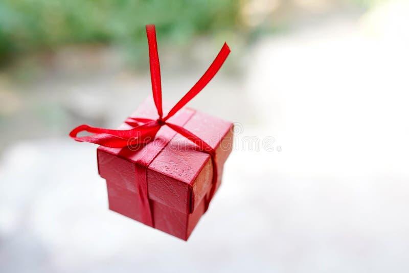 Czerwony prezenta pudełko na lekkim tle z kopii przestrzenią, niespodziance dla urodziny lub valentine dniu, obraz stock