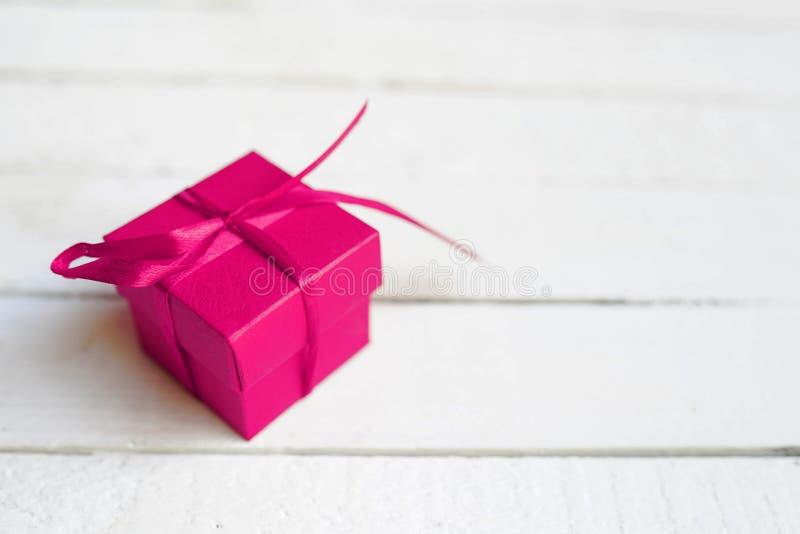 Czerwony prezenta pudełko z faborkiem na białym drewnianym tle kosmos kopii zdjęcie stock