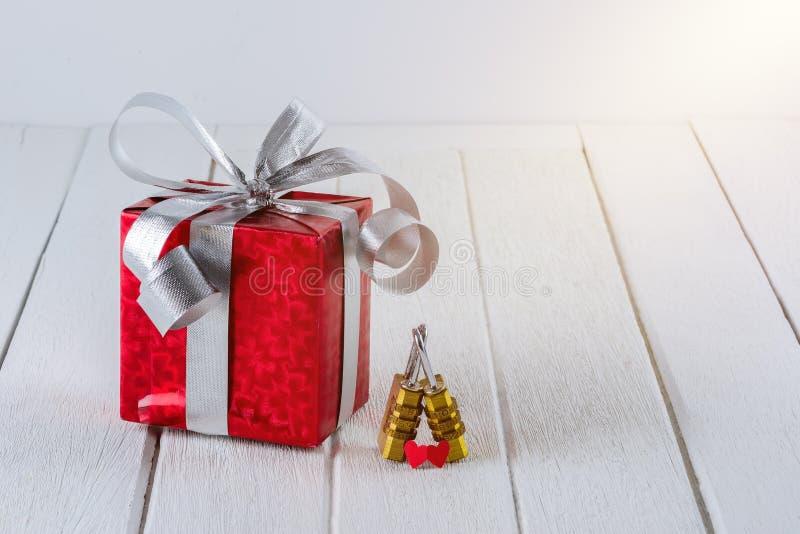 Czerwony prezenta pudełko z Kierową kształta i pary kombinacji złotą kłódką na białym drewnianym stole zdjęcia stock