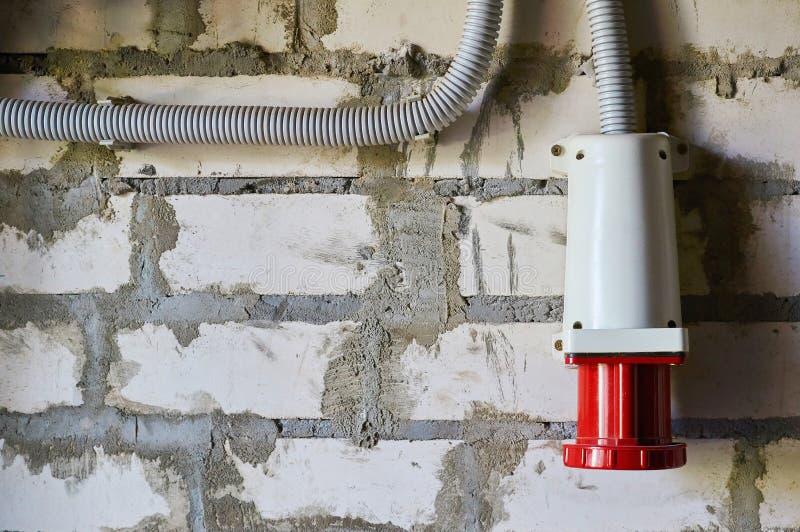 Czerwony przemysłowy włącznik dla elektrycznych urządzeń lokalizować na ściana z cegieł obrazy stock
